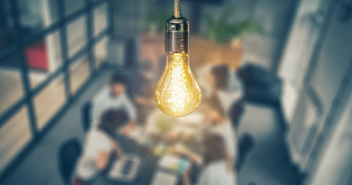 Lightbulb-above-office-business-management-meeting-iQ-academy