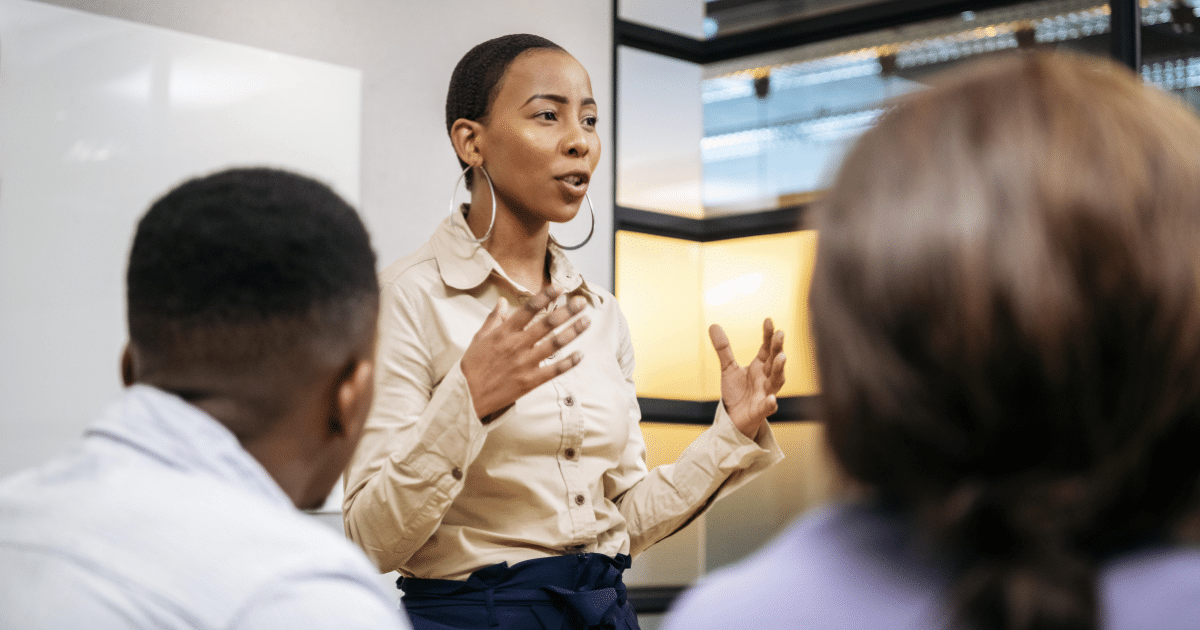 image-of-woman-confidently-speaking-in-busisness-meeting-iq-academy